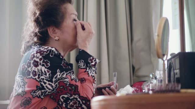 vidéos et rushes de senior dame appliquant make up - miroir ancien