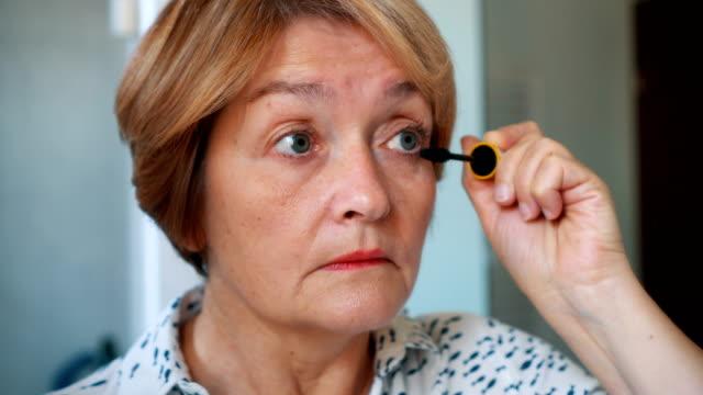 Senior lady applying mascara