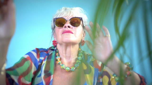 vídeos de stock, filmes e b-roll de a senior lady dancing and catching bubbles - pegar