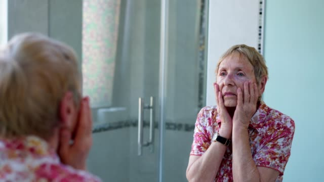 senior lady examines her skin condition - mirror stock videos & royalty-free footage