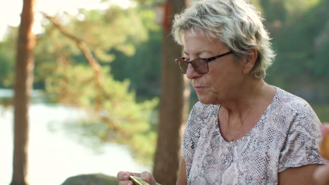 senior lady having a picnic in a forest - non urban scene stock videos & royalty-free footage