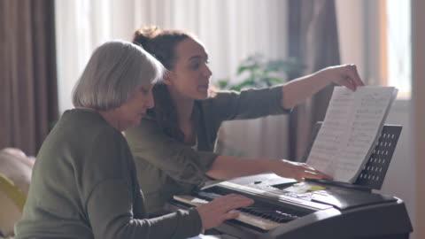 senior lady learning synthesizer with young female volunteer - musikinstrument bildbanksvideor och videomaterial från bakom kulisserna