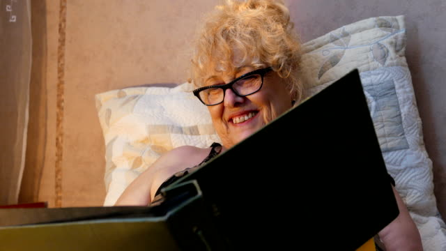 Senior lady looking at an old photo album brings back memories