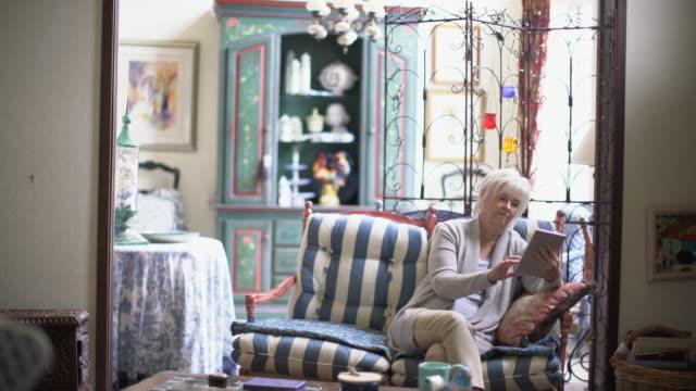 WS Senior lady looking at her digital tablet in her living room
