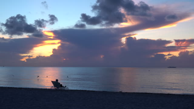 Senior lady on a chaise longue on the beach watching sunrise