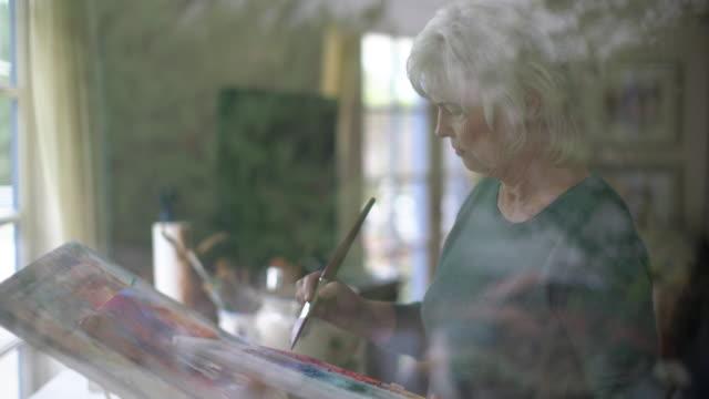 cu senior lady painting in her art studio - pensionamento video stock e b–roll