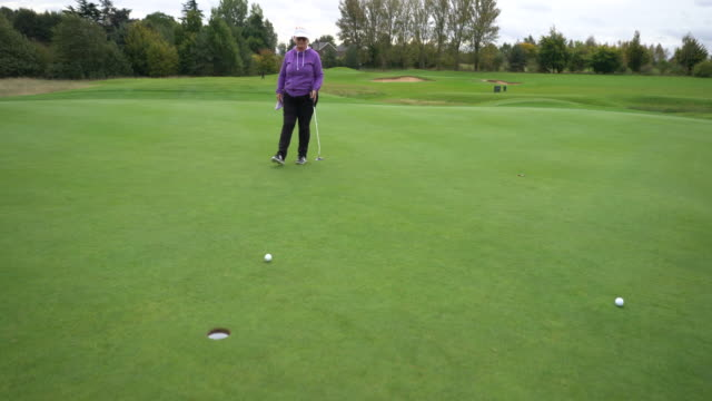 a senior lady putting the ball into the hole. - sonnenschild stock-videos und b-roll-filmmaterial