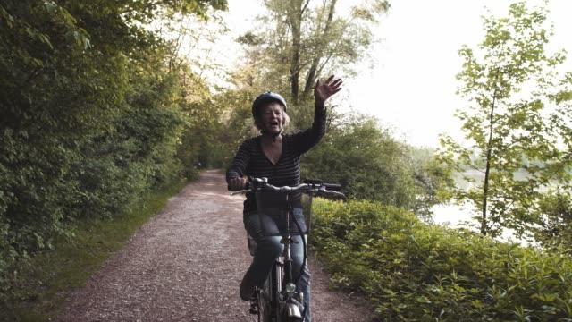 vídeos de stock e filmes b-roll de senior lady riding a bicycle and waving - ensolarado