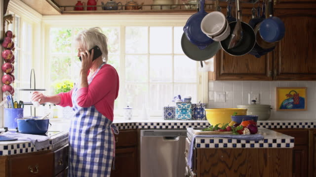 MS Senior lady talking on her phone in the kitchen