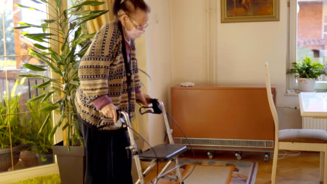 senior lady with a rollator walking in house during coronavirus home quarantine - chair stock videos & royalty-free footage