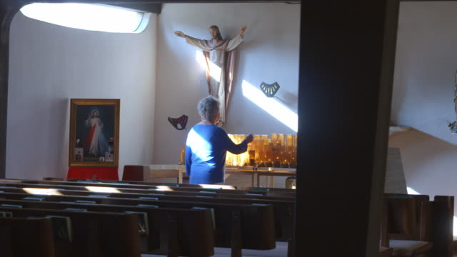 pan senior lady worshipper in catholic church lights up a votive candle burning next to a full rack of votive prayer candles placed underneath statue of jesus - worshipper stock videos & royalty-free footage