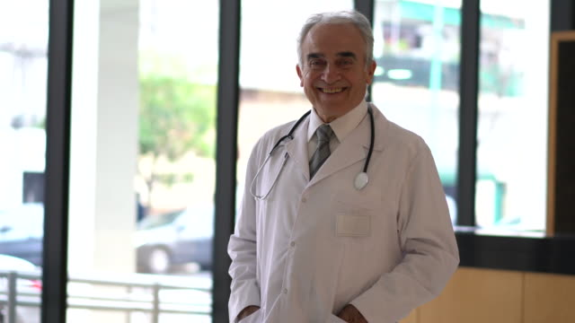 senior latin american doctor at the hospital facing camera smiling very cheerfully - lab coat stock videos & royalty-free footage