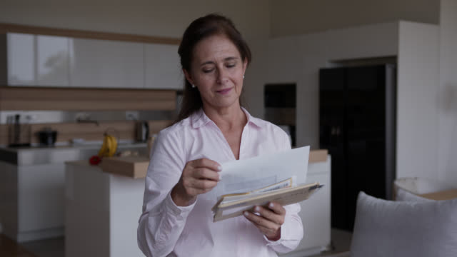 senior latin american woman at home checking her mail - correspondence stock videos & royalty-free footage