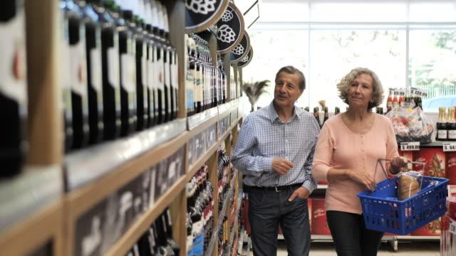 vídeos y material grabado en eventos de stock de compras familiares latinas en supermercado - comprando cerveza y vino - super slow motion