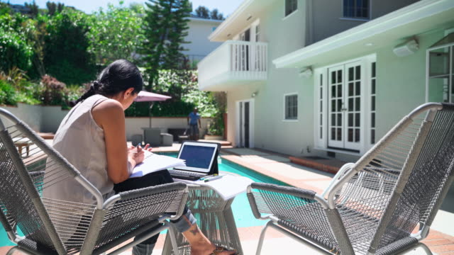 senior latino couple at the backyard of his house. the woman working with financial documents with printed reports and a tablet, the man cleaning the pool in the backdrop. - patio stock videos & royalty-free footage