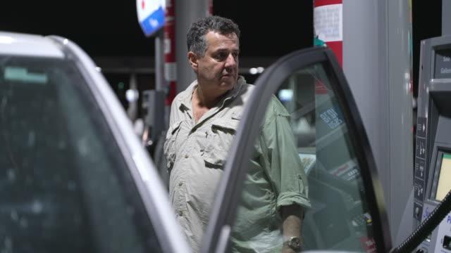 vídeos y material grabado en eventos de stock de el hombre latino mayor alimenta ndo el tanque del auto en la gasolinera en la noche. - bomba de combustible