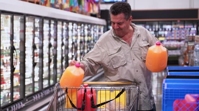 stockvideo's en b-roll-footage met senior latino man het kopen van een sap in een supermarkt. - 65 69 jaar