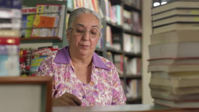 vídeos y material grabado en eventos de stock de senior librarian working in a library  - árbitro