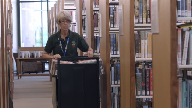 ms ts senior library employee  pushes book cart down main aisle lined with shelves as she takes a book from cart and returns it back to original shelf / rancho mirage, california, usa - rancho mirage stock videos & royalty-free footage