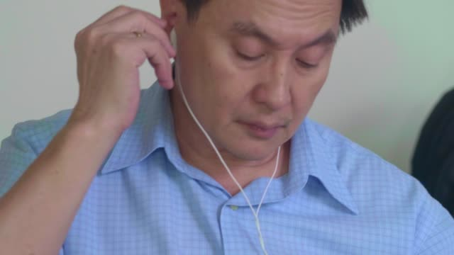 stockvideo's en b-roll-footage met senior luisteren podcast - in ear koptelefoon