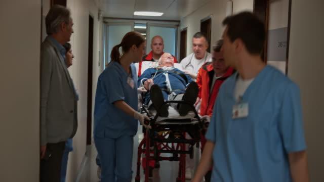 vidéos et rushes de ds senior male being brought into emergency by paramedics - secouriste