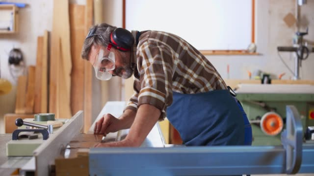 ds senior male carpenter cutting planks on the table saw in his workshop - carpentry stock videos & royalty-free footage