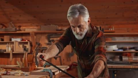 vídeos y material grabado en eventos de stock de carpintero masculino senior usando un cuchillo de tiro en su taller - pasatiempos