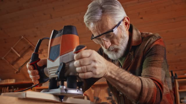 senior male carpenter using a jigsaw to cut a piece of wood in an odd shape in the shop - work tool stock videos & royalty-free footage