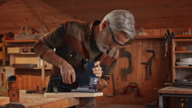 senior male carpenter using a jigsaw to cut a piece of wood in his workshop - hobbies stock videos & royalty-free footage