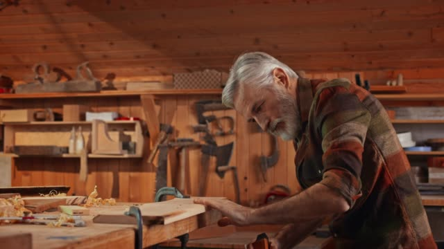 senior male carpenter using a plane in his workshop - filmato non girato negli usa video stock e b–roll