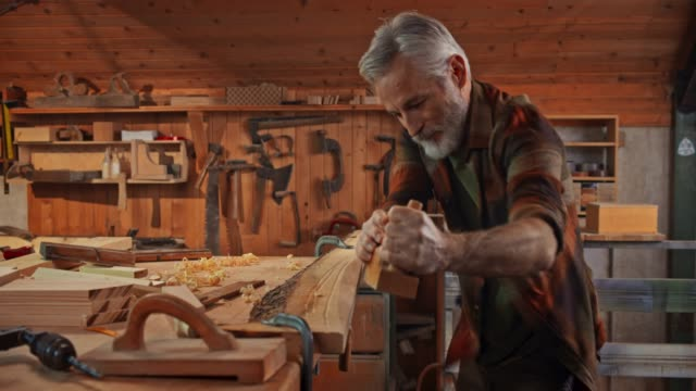 senior male carpenter using a plane to square a board in his shop - filmato non girato negli usa video stock e b–roll