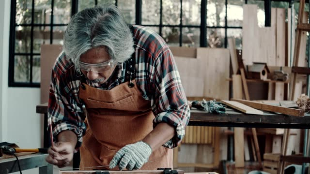 senior male carpenter working on circular wood saw - carpentiere video stock e b–roll