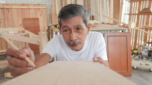 senior male carpenter works at home during the day, a senior male carpenter using a pencil with a stick on the table. - hot desking stock videos & royalty-free footage