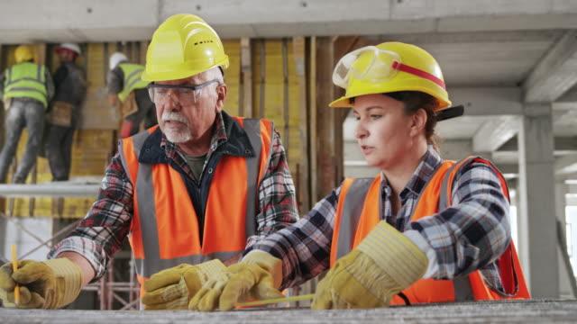 operaio edile senior che insegna un'apprendista donna in cantiere - strumento di misura video stock e b–roll