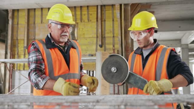 vídeos de stock, filmes e b-roll de trabalhador da construção masculino sênior que ensina um aprendiz masculino como cortar através do engranzamento de aço - serra circular