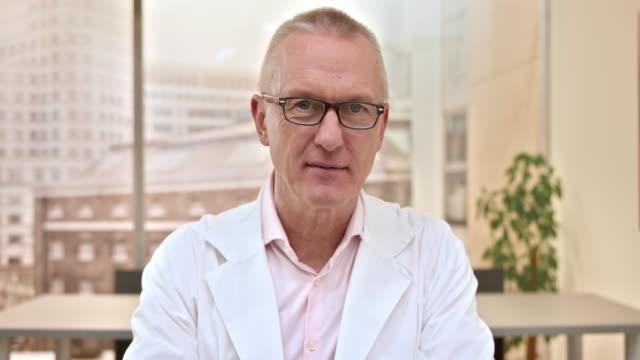 stockvideo's en b-roll-footage met senior mannelijke arts op een video-oproep uit zijn ambt - laboratoriumjas