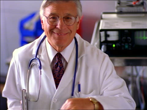 PORTRAIT senior male doctor with stethoscope + eyeglasses smiling at camera