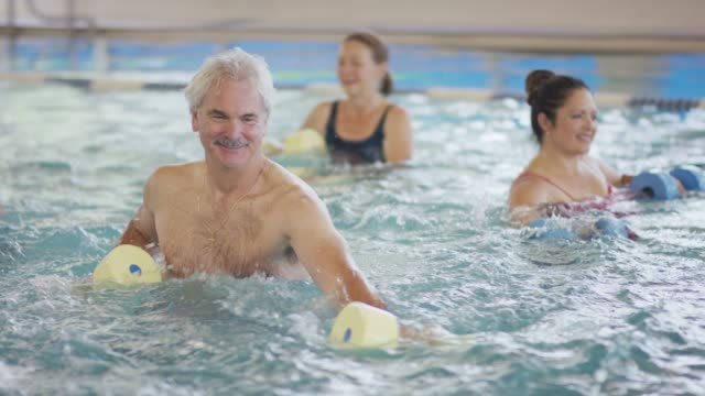 senior male doing water aerobics - 50 59 years stock videos & royalty-free footage