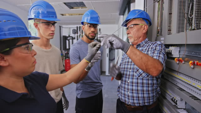 senior male electrician showing his three apprentices how to strip the wires in the electrical panel - electrician stock videos & royalty-free footage