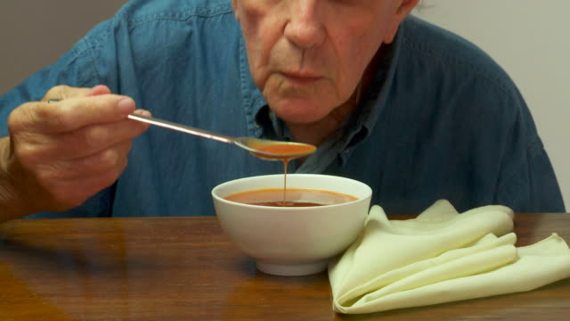 senior male enjoying a bowl of tomato  soup - soup stock videos & royalty-free footage