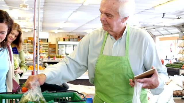 senior male grocer is helping mother and daughter at check out at produce market - assistant stock videos and b-roll footage