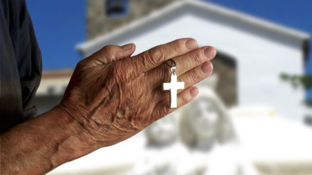 senior male hands with silver cross praying in front of a church