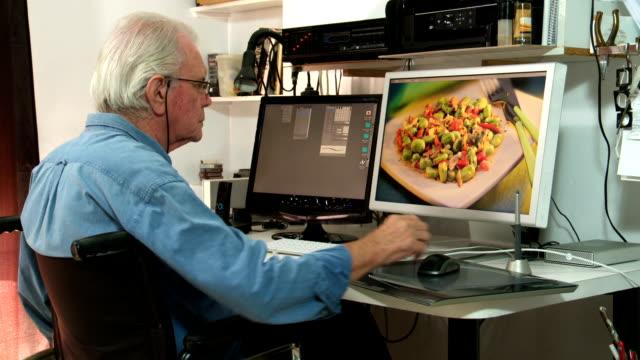senior male in wheelchair retouching artwork on computer