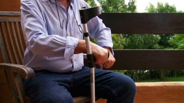 Senior male leaves patio chair aided by crutch