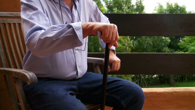 Senior male leaves patio chair aided by walking stick.