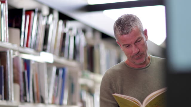 senior male looking for a book in library - post secondary education stock videos & royalty-free footage