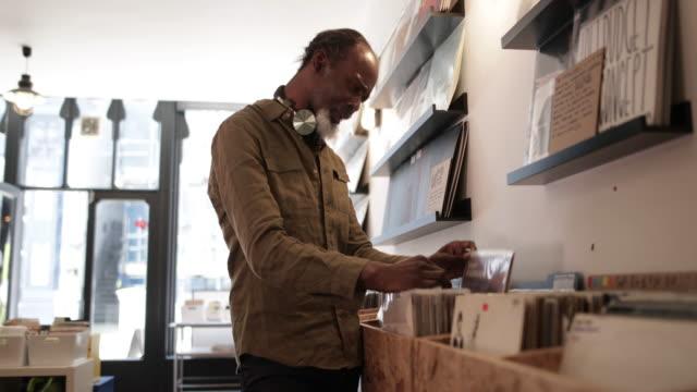 vídeos y material grabado en eventos de stock de senior male looking for records in a store - tienda de discos
