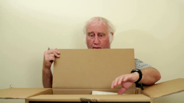 vídeos de stock e filmes b-roll de sénior masculino looks dentro de caixa grande procura de plástico - encontrar