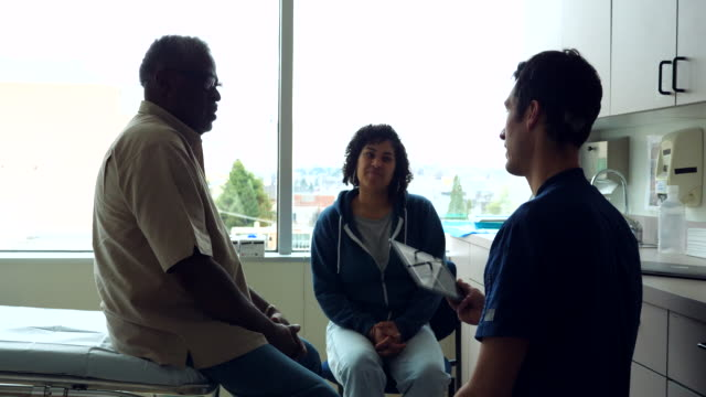 ms senior male patient and adult daughter consulting with male nurse during check up in exam room - adult offspring stock videos & royalty-free footage