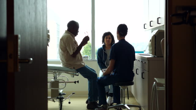 ms senior male patient and adult daughter consulting with male nurse during check up in exam room - responsibility stock videos & royalty-free footage